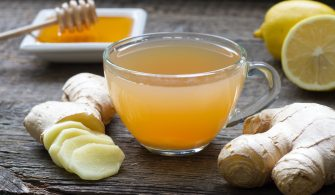 Ginger homemade tea infusion on wooden board with lemon